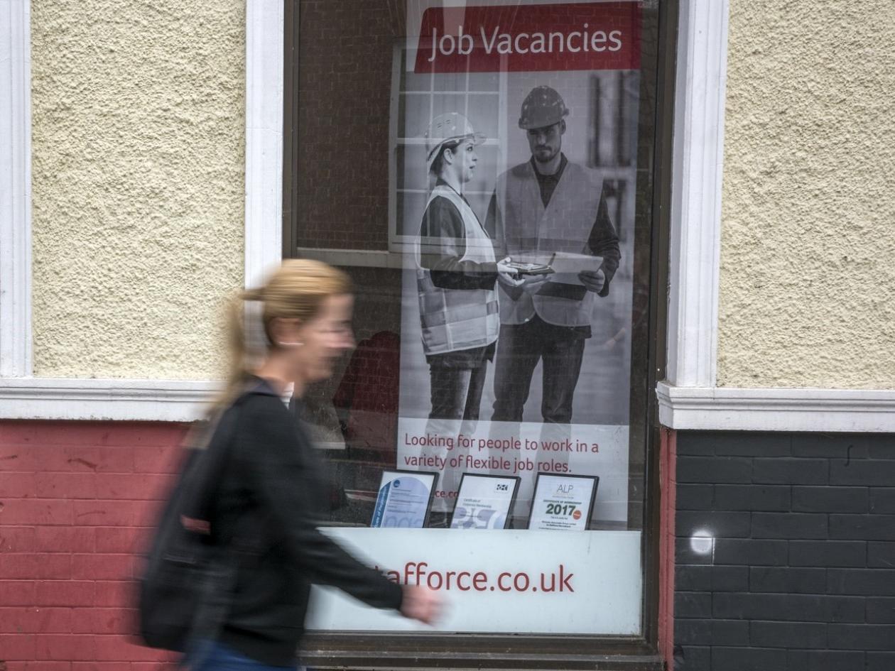 woman walking past job centre window