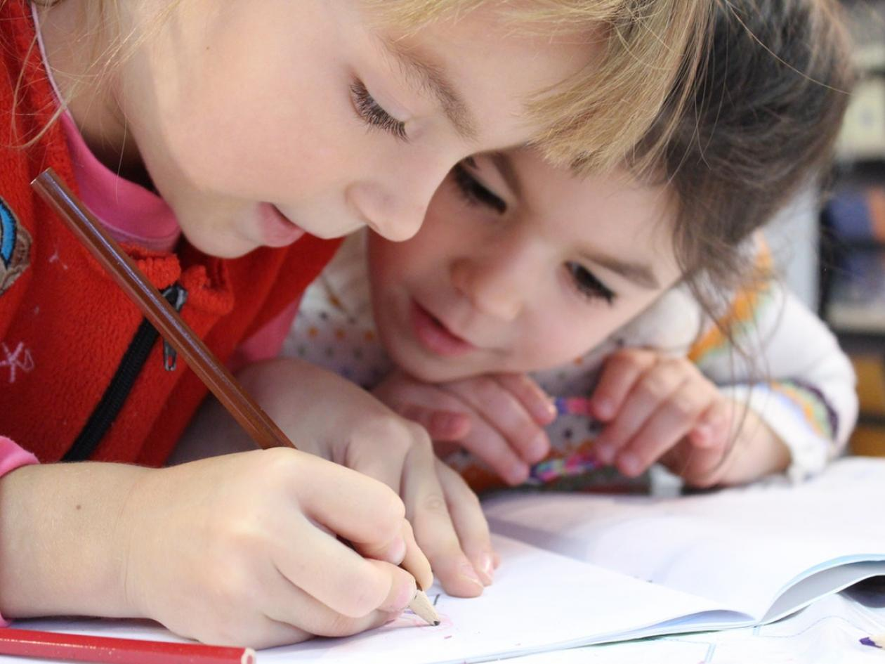 Photo of two children writing