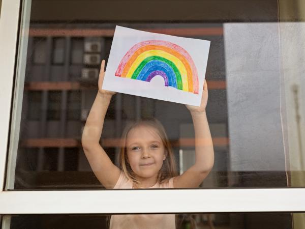 Photo of girl at window with rainbow drawing